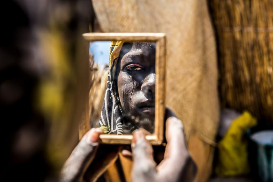 Una mujer que acude a una clínica prenatal de MSF en Diffa, Níger, mira su reflejo en un espejo de mano ©Juan Carlos Tomasi/MSF