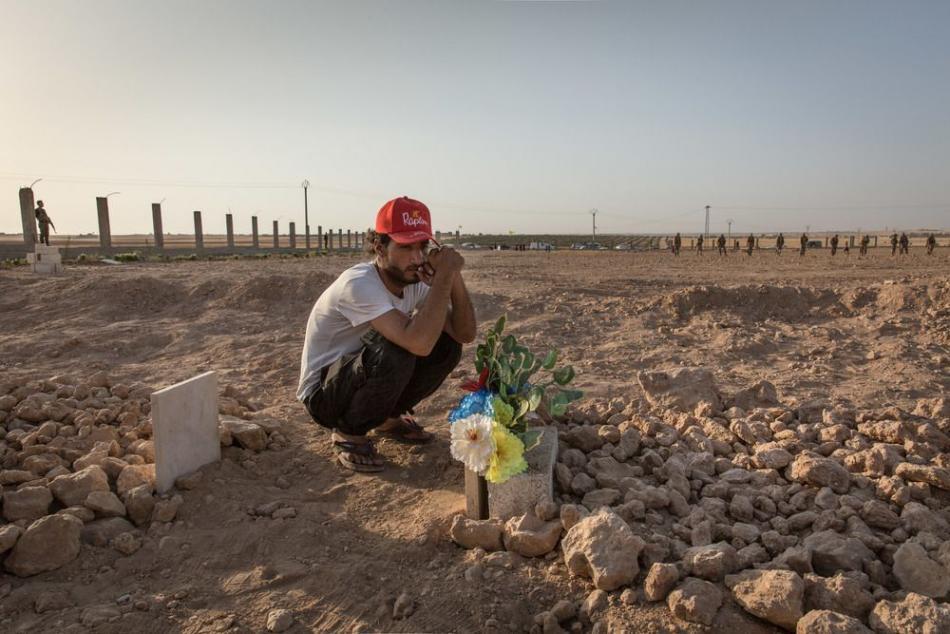 Tal Abyad, Siria - Ismael se sienta en la tumba de su primo y amigo, Hout, quien fue asesinado dos días antes durante la batalla por Raqqa, Siria ©Chris Huby