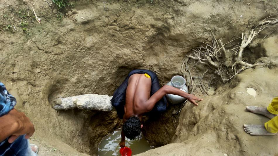 Un hombre sacando agua de un pozo que fue cavado a mano. © Paul Andrew Jabor/MSF