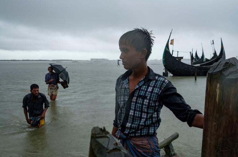 Un niño de Bangladesh observa a los refugiados rohingya que llegan bajo una lluvia torrencial en un paso fronterizo en el río Naf, cerca de Teknaf, después de haber escapado de Myanmar. Casi 650.000 rohingyas han huido a Bangladesh desde Myanmar