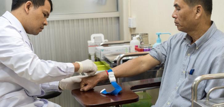 Din Savorn, de 50 años, recibe un análisis de sangre por parte de un técnico de laboratorio en la clínica de MSF Hepatitis C en el Hospital Preah Kossamak en Phnom Penh, Camboya, 20 de abril de 2017. ©Todd Brown/MSF