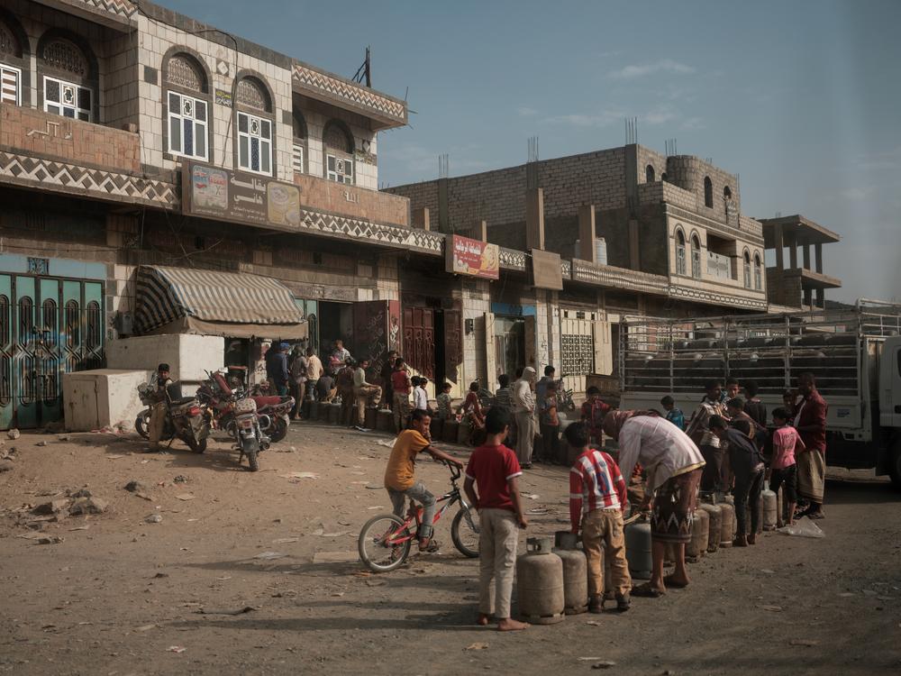 Hombres y niños hacen cola para recibir combustible en Yemen