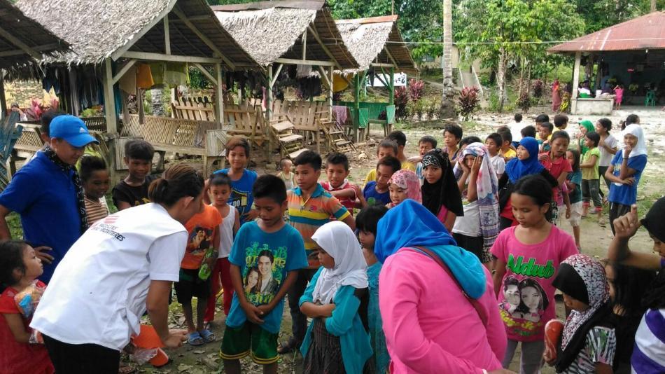 Un consejero de salud mental de MSF habla con los niños durante la distribución de artículos no alimentarios, incluidos zapatos y mantas. Más de 200 personas murieron a raíz del tifón Tembin y las inundaciones repentinas y deslaves resultantes, con muchos