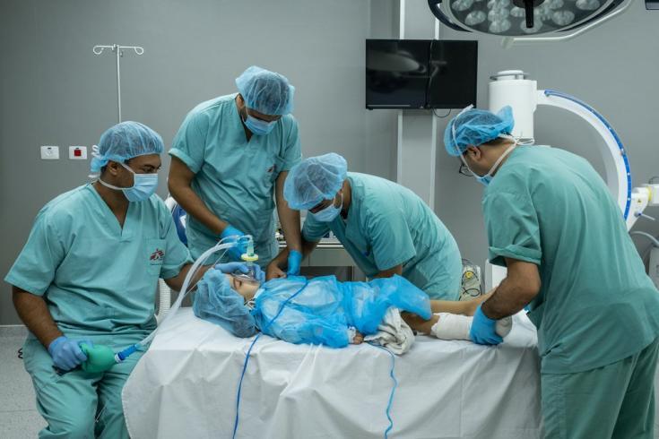 Dentro del hospital Al-Awda, el anestesista de nuestra unidad de reconstrucción de extremidades duerme a Hala antes de comenzar la cirugía. Gaza, agosto de 2021