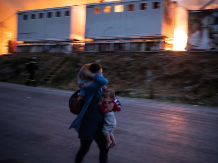 Una mujer escapa con su bebé de los incendios en el campo de Moria, el 9 de septiembre de 2020. Isla de Lesbos, Grecia