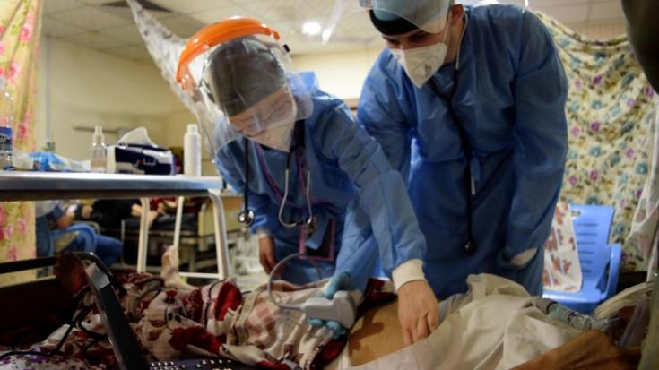 Un médico de MSF ofrece asesoramiento técnico sobre cómo examinar a un paciente con COVID-19 a un médico iraquí que trabaja con la Dirección de Salud de Bagdad, en la unidad de cuidados respiratorios del Hospital al Knidi.