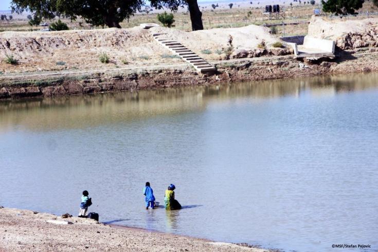 """Niños recogiendo agua del lago artificial o """"estanque"""" de Pulka. Debido a que una de las unidades de tratamiento de cloro no funciona, no suele estar limpia. 02/02/2021"""