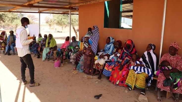 Uno de nuestros promotores de salud habla con un grupo de mujeres mientras esperan a ser atendidas en la sala de maternidad del hospital de Gorom Gorom, en la región del Sahel. Burkina Faso, febrero de 2021