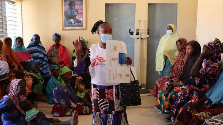 Una de nuestras promotoras de salud brinda educación sobre temas relacionados con salud e higiene a un grupo de mujeres que esperan ser atendidas en la sala de maternidad del centro de salud de Wendou, en la región del Sahel. Burkina Faso, febrero de 2021