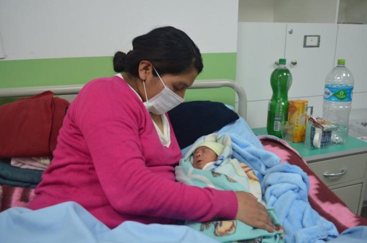 Una paciente en sala de post parto junto a su bebé, en el Centro de Salud San Roque en la ciudad del El Alto. Bolivia, abril de 2021