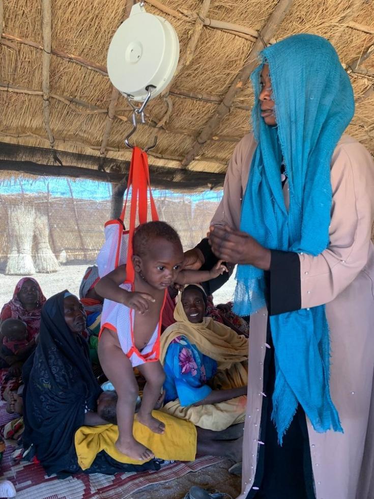 Nuestro equipo médico pesa a un niño con desnutrición en la clínica que instalamos en la aldea de Dilli. Sudán, abril de 2021