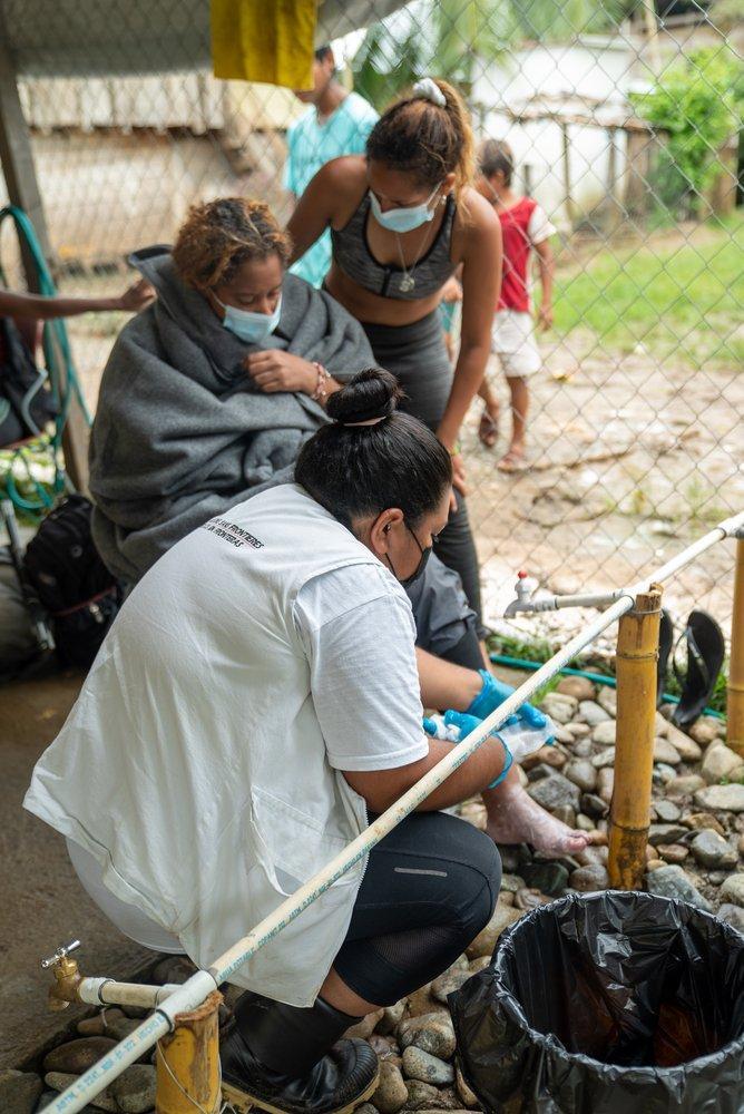 Solange se separó de su madre en la selva del Darién y llegó dos días antes que ella a Bajo Chiquito, Panamá. El día de la foto, el 12 de junio de 2021, se reunieron nuevamente. Nuestra enfermera Lucero prepara el material para lavar y curar los pies .