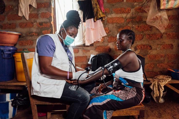 Enfermera tomando la presión arterial de una mujer en Sierra Leona