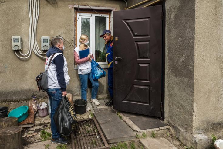 Dos integrantes de nuestros equipos de apoyo, Oksana Vykhivska y Oleksandr Vovkogon (trabajadora social y enfermero), le entregan paquetes de comida en su casa al paciente de TB Vitalii Gorbachov, de 56 años, en el distrito de Chudniv.