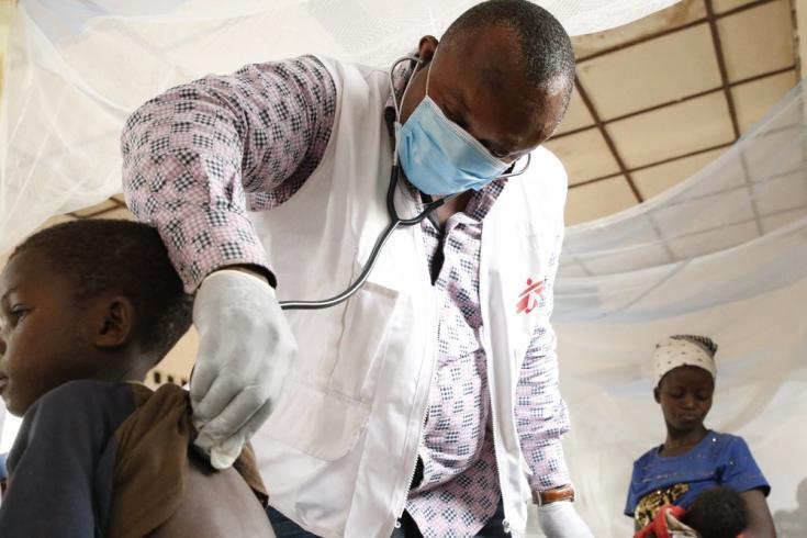 Theophile, médico del equipo de emergencias de MSF, examina a un niño con sarampión en el hospital general de Bosobolo. Febrero de 2021