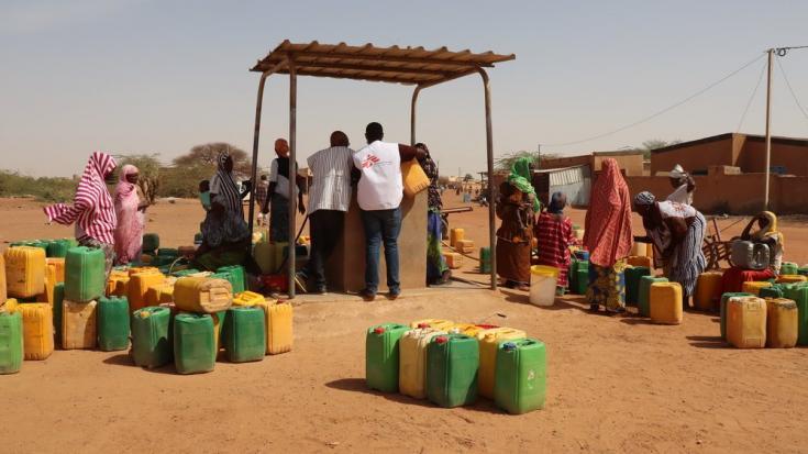 Nuestro personal ayuda a las personas desplazadas a recoger agua limpia en un punto de agua en el distrito de Gorom Gorom, en la región desértica del Sahel, al norte de Burkina Faso. Febrero de 2021