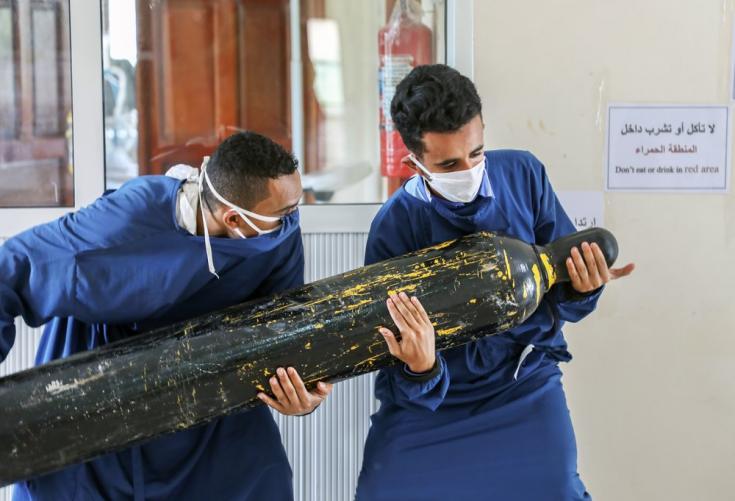 Dos trabajadores del centro Al-Sahul de COVID-19 están tratando de trasladar una botella de oxígeno al interior de la Unidad de Cuidados Intensivos.