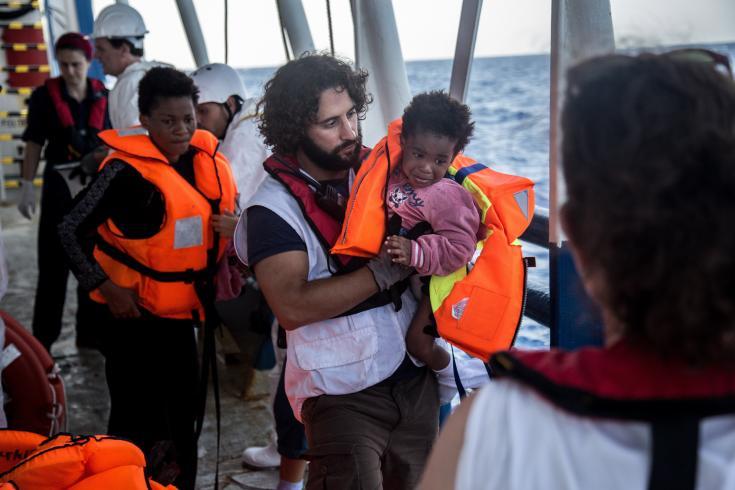 Juan Mátias Gil, coordinador general del barco Dignity I, ayuda a subir a bordo a Richard, de Nigeria, recién rescatado junto a sus padres de un bote a punto de hundirse en el mar Mediterráneo. Septiembre de 2015.