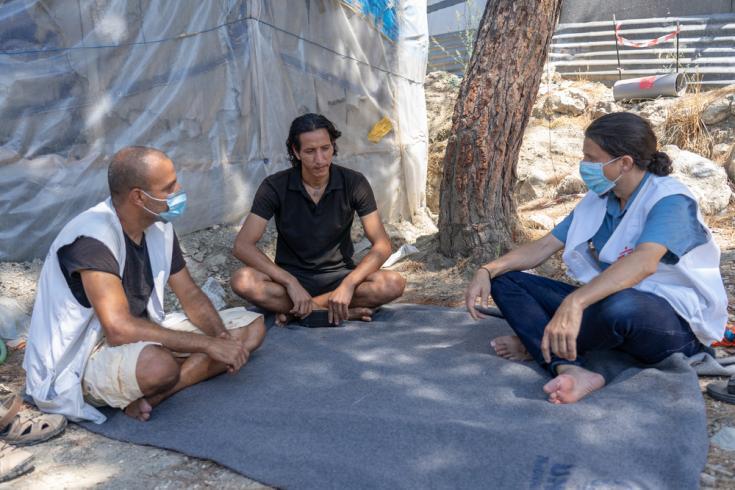 Director general de MSF Suiza (derecha), habla con Ali Al Ahmed (centro), un sirio de 30 años que vive en el campo de refugiados de Vathy en Samos desde noviembre de 2019.