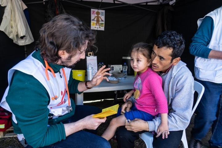 El médico de Médicos Sin Fronteras, Stefanos Tsallas, vacuna a un niño contra la neumonía en un campo de refugiados en Grecia.