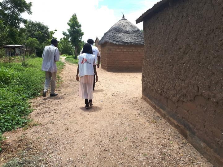 Un promotor de salud y un especialista en agua visitan un distrito para identificar posibles fuentes de propagación de cólera.