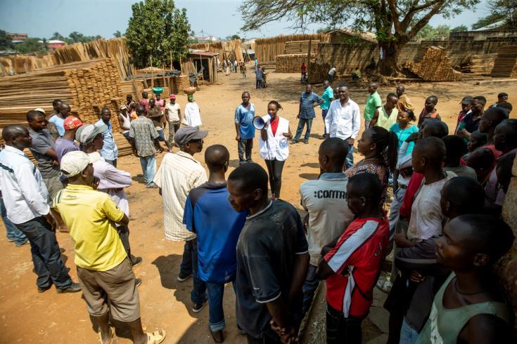 """Nicole Niyoyankunze, promotora de salud de Médicos Sin Fronteras, junto a carpinteros del distrito de Bwiza. La expansión de los criterios de admisión por trauma accidental condujo a un aumento en la asistencia a la instalación de """"L'Arche de Kigobe""""."""