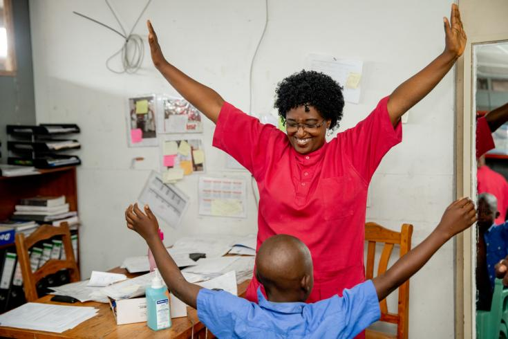 """Un fisioterapeuta de MSF en el centro de traumatología de MSF """"L'Arche de Kigobe"""" le da ejercicios de rehabilitación a una paciente joven a quien le quitaron el yeso del brazo."""