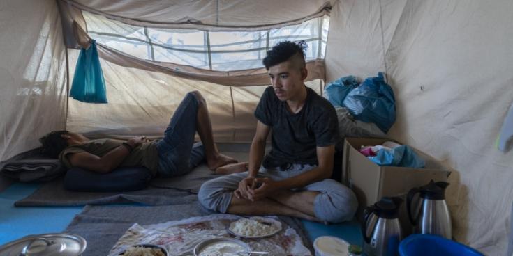 Dos jóvenes afganos sentados en una tienda de campaña que deben compartir con familias desconocidas para ellos en el Olive Groove cercano al campo de Moria, en la isla de Lesbos.