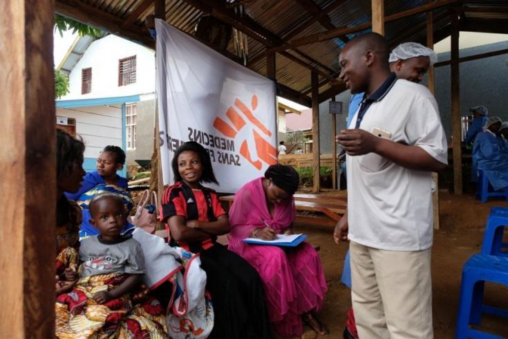 El trabajador sanitario Joseph habla con las personas que esperan recibir la vacuna en República Democrática del Congo.