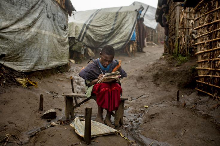 Una niña de 12 años en el campo de desplazados internos de Katale, en el territorio de Masisi. Hace su tarea durante las últimas horas del día, frente a su casa.