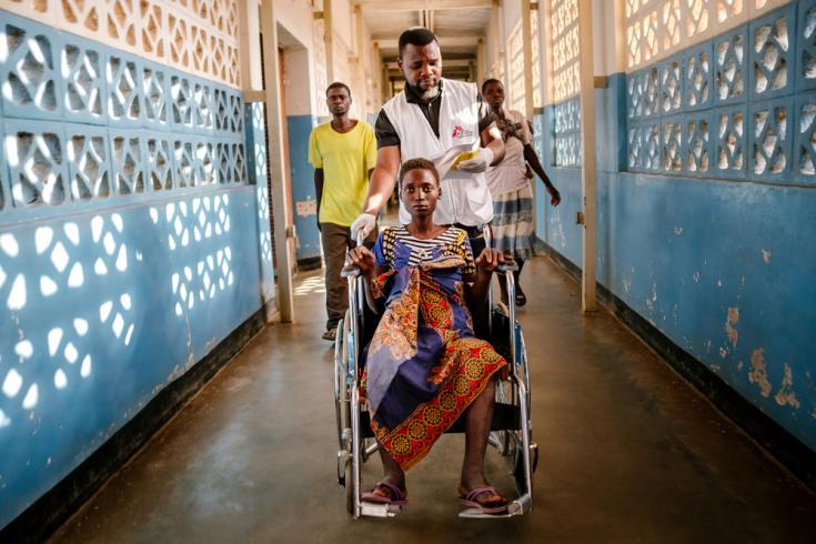 Nelson Chidanti ayudando a Lita a trasladarse en en silla de ruedas hacia otra parte del Hospital del Distrito de Nsanje