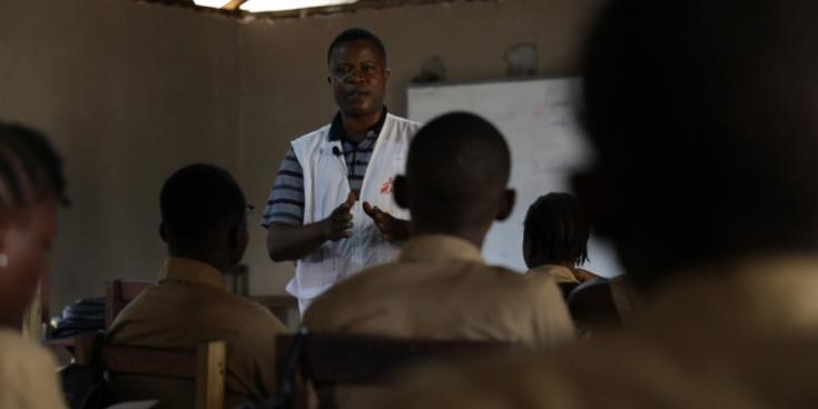 Abraham S. Kollie, un trabajador psicosocial de Médicos Sin Fronteras, hablando con unos estudiantes sobre la epilepsia. Los niños con epilepsia a menudo son excluidos en la escuela debido al estigma.