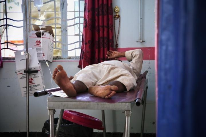Dentro de la sala de emergencias del Hospital General al-Thawra apoyado por MSF, un paciente se encuentra en la cama después de haber sido estabilizado.