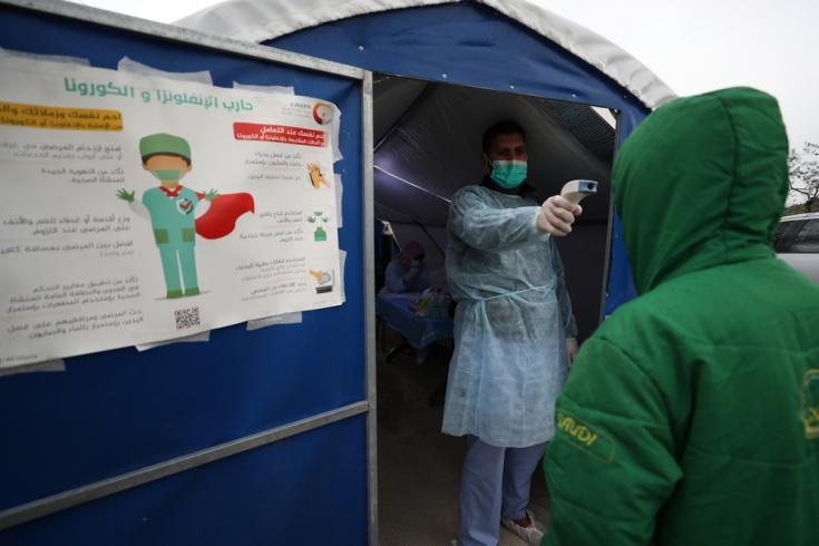En un hospital que apoyamos en el noroeste de Siria, un médico verifica la temperatura de un paciente en un espacio para identificar síntomas de COVID-19, para luego trasladarlos a observación si es necesario y llamar a una ambulancia y realizar el test.