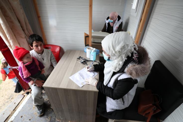 Una enfermera de MSF habla con un niño que trajo a uno de sus familiares para una consulta, en la clínica móvil de MSF, en un campamento de desplazados internos en el noroeste de Siria.