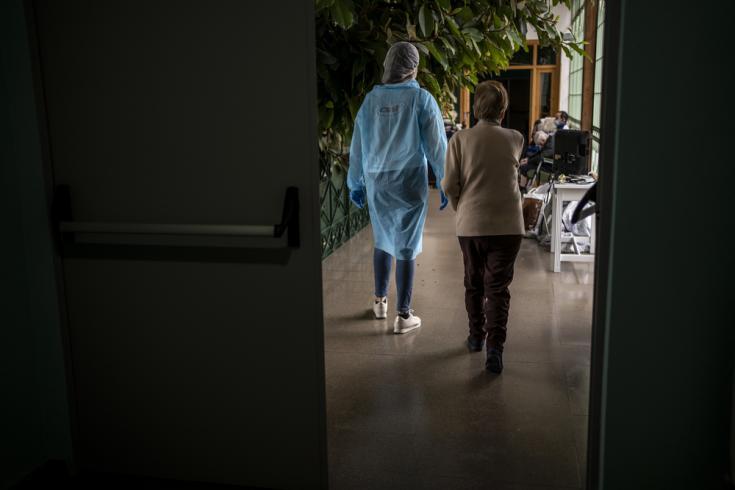 Una trabajadora de MSF acompaña por un pasillo a una residente de la Residencia Nuestra Señora de las Mercedes de El Royo (Soria), en España.