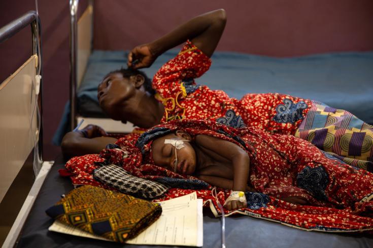 Con apenas dos años y medio de edad, Ester recibe tratamiento en la Unidad de Cuidados Intensivos de la sala de sarampión de MSF. Su madre Evelyne está acostada a su lado, en el Hospital Bossangoa, República Centroafricana.