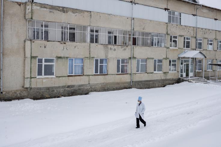 Un médico del Ministerio de Salud local camina frente al hospital Aydarken en la región suroeste de Kadamjay de Kirguistán.