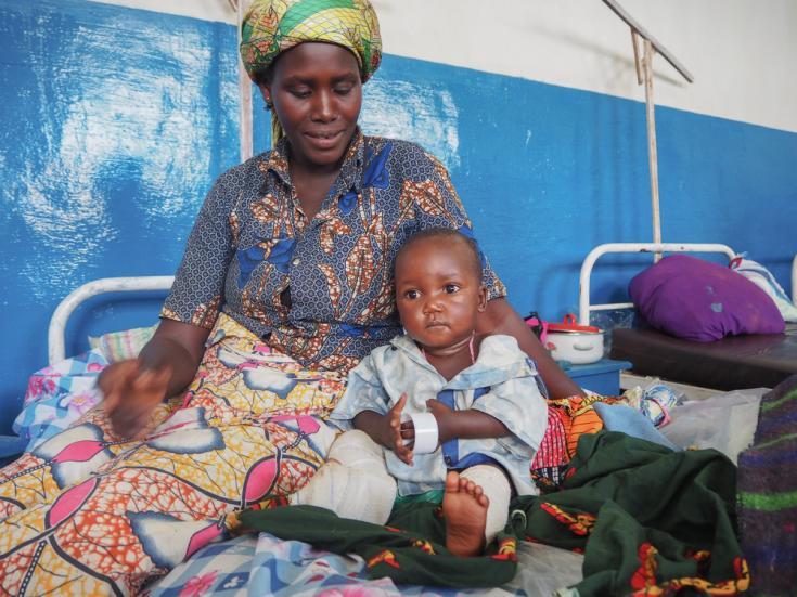 Bahati Maki Jospin, un niño de 15 meses de edad junto a su tía. Es la víctima más joven del ataque en la aldea de Jissa el 17 de mayo. El bebé estaba atado a la espalda de su madre cuando una bala los alcanzó, hiriendo su pierna y matando a su madre.