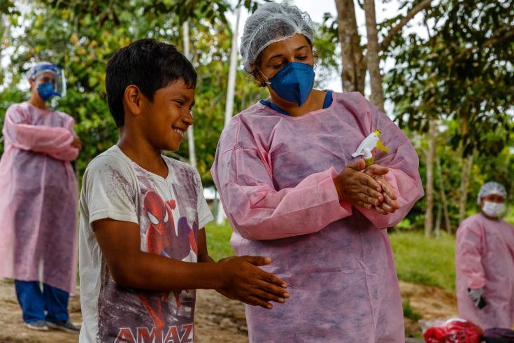 La enfermera Nara Duarte enseña a un niño la forma correcta de realizar la higiene de manos en una comunidad del Lago Mirini, Brasil.