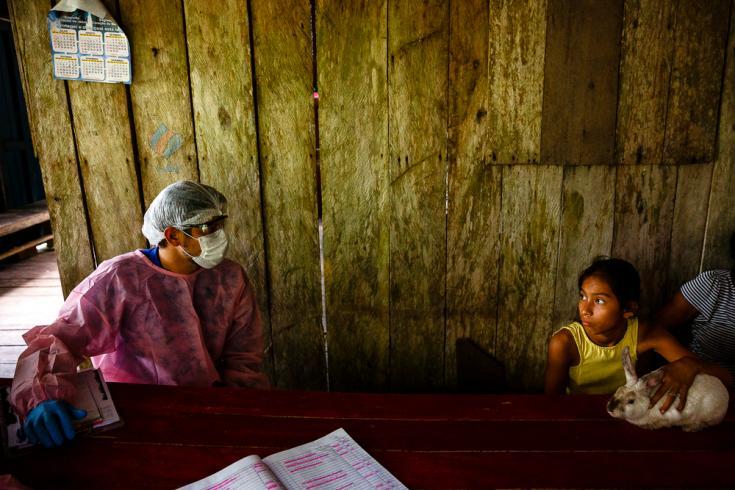 Un trabajador del sistema de salud municipal de Brasil habla con una familia durante las visitas a domicilio que se realizaron en la región del lago Mirini.