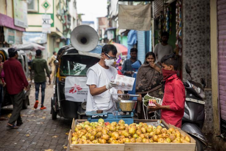 Ganpat, trabajador de MSF entrega un kit de higiene (10 mascarillas y 8 jabones) a los vendedores ambulantes en las calles de los barrios del este de Govandi.