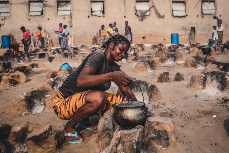 Una joven prepara una cena para su familia en un área de cocina al aire libre del campamento de Abagana para personas desplazadas en el estado de Benue. Nigeria, junio de 2020.