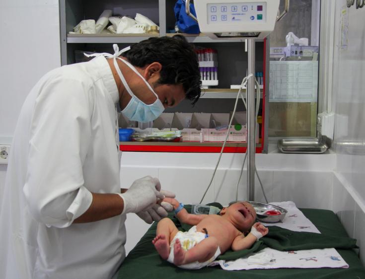 Un médico de Médicos Sin Fronteras inserta una cánula en la mano de un bebé para una transfusión intravenosa en la unidad de recién nacidos del hospital de la sede del distrito de Timergara, Pakistán.