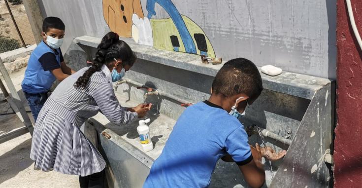 Mariam Qabas (Supervisora de Promoción de la Salud) está llevando a cabo una actividad de promoción de la salud sobre COVID-19 con niños en una escuela en Al-Ramadin, una aldea palestina ubicada al suroeste de Hebrón (Cisjordania).