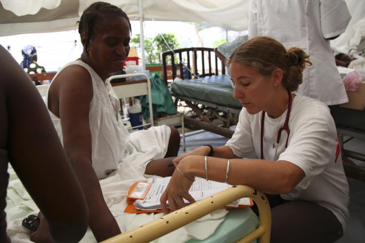 Carolina Nanclares atiende a una paciente en Haití. Los servicios para pacientes ambulatorios y para pacientes hospitalizados se realizaron debajo de carpas, ya que el hospital sufrió graves daños.