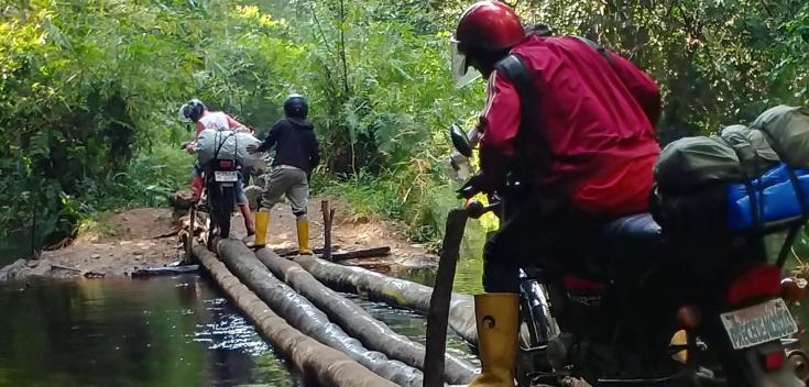 Vera, en motocicleta en medio de la selva, cruzando un pequeño puente hecho de troncos de árboles.