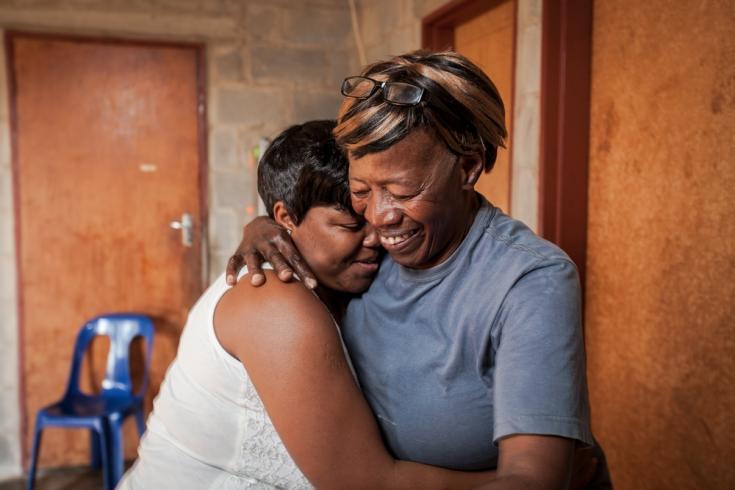 La cuidadora comunitaria Nonhlanhla Ngema en Sudáfrica abraza a un miembro de su grupo con VIH positivo.