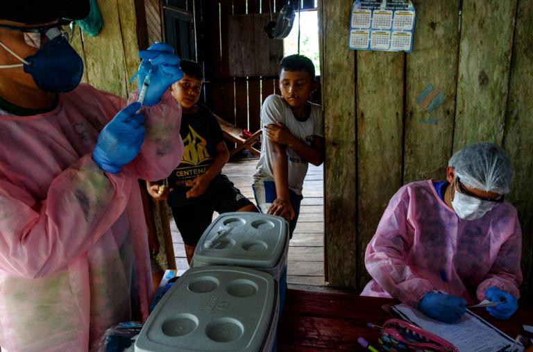 Personal de MSF y del sistema de salud municipal realiza vacunas de rutina en una casa familiar a orillas del lago Mirini, en la región amazónica de Brasil.