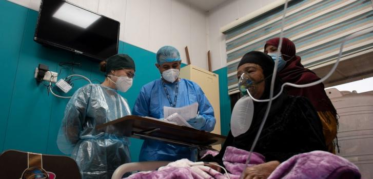 Una paciente de COVID-19 recibiendo oxígeno en la sala de hospitalización de MSF dentro del hospital al Kindi, en Bagdad. Las enfermeras de MSF revisan su condición y dan instrucciones al cuidador (su hijo) sobre cómo asistirla.